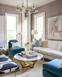living room design | lavender grasscloth wall coverings | lucite chandelier | blue velvet slipper chair | round brass coffee table with marble top | blue print | blueprintstore.com