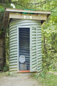 pic of outhouses  - An outhouse made with a thick pipe sitting in the forest - JPG
