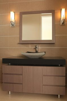 The lovely, smooth finishes in this modern bathroom channel spa and Asian influence. Large, neutral wall tile creates the backdrop for the woodgrain storage drawers with an elevated black countertop. The black brings a beautiful contrast to the warm, neutral color palette. The vessel sink adds a textured look.