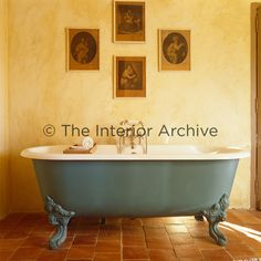 A blue-grey roll top bath stands on the terracotta tiled floor in the bathroom. - Dordogne