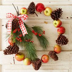 This eye-catching fall wreath will brighten your front door with two-tone apples and bold red berries. Find more fall wreaths here: http://www.bhg.com/thanksgiving/outdoor-decorations/holiday-wreaths/?socsrc=bhgpin090514applepineconewreath&page=12