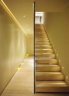 #iluminacao - Próxima da porta de entrada, a escada é um marcante cartão de visita. Lâmpadas bipino produzem uma luz suave que demarca o caminho, como nos cinemas.