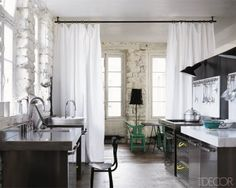 In her Paris loft, Italian designer Paola Navone installed floor-to-ceiling curtains between the kitchen and dining area—a chic and easy way to divide the open space. Sectional units from her Pastasciutta line for Ciatti a Tavola, topped with steel and marble, create an industrial look.