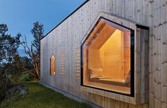 Perforated shutters in local pine blend with this house's facade in Norway.