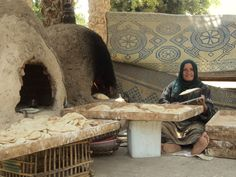Woman making typical Egyptian bread... in a very sunny atmosphere...