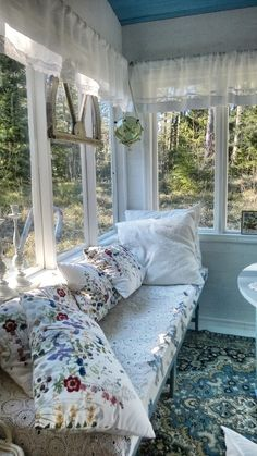 Veranda. Blue painted furniture, flowery pillows, lace curtains.