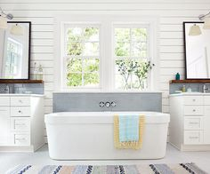 Light-filled and inviting, the newly built master bath features farmhouse-appropriate shiplap walls, a focal-point soaking tub, and separate vanities.