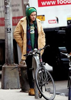 Green Packer's hoodie, floral blue and red shirt, wheat thick coat, green beanie, you go Harry Styles.