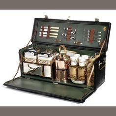 A large impressive Edwardian 'Coracle' four-person picnic set, leather-cloth case with nickel-plated with lid, fall-front opening to reveal interior fitted with copper kettle and burner, two large drinks bottles, a smaller drinks bottle, two Coracle sandwich boxes, large/small food tins, ceramic cups, saucers, butter jar, stacking glasses, four rectangular enamel plates, silver vesta case and cutlerysuitable for early Bentley, Rolls-Royce or similar fine touring car Sold for £4,678 inc…