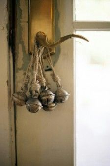 Small , round bells tied with twine , hanging over a door handle.