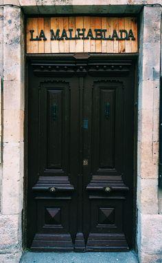 """En la calle Meléndez, Salamanca, se encuentra """"La Malhablada"""". Un edificio, antes una antigua pensión, que hoy funciona como espacio de cultura y ocio entre los actores del teatro y el público. Utiliza tipografía Egipcia en su cartel, lo cual es ideal para representar la identidad del lugar: clásico pero también moderno."""