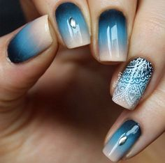 A magical looking blue gradient nail art design. Blue and nude polishes are used to create the gradient effect. White polish is then used for the lace details on top with a silver bead on top.