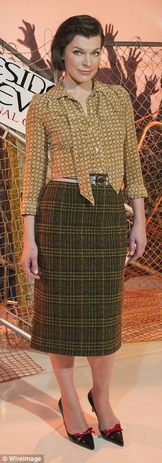 Bold look:The 41-year-old tucked a yellow printed blouse into a plaid midi-skirt which hugged her lean figure. She added a belt and pointy toed pumps featuring red decorative bows