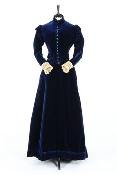 A sapphire blue velvet day dress by Miss Blazeby of Portman Square, late 1880s. the waistband also with 74 Baker Street address, with embroidered buttons, Elizabethan style references to the shoulders, lace cuffs