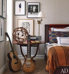 19th c. townhouse NYC. Collings and Gibson Les Paul guitars stand alongside a 19th-century French tilt-top table in bedroom.