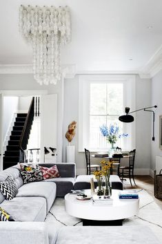 Eclectic London townhouse with a low sectional sofa, glass chandelier, task arm sconce & chivari chairs