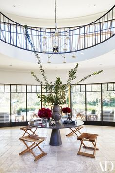 Kourtney Kardashian's foyer with high ceilings, a modern table, a retro chandelier, and stools