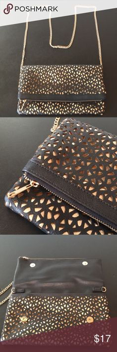 """Laser-Cut Clutch With Gold Accents Perfect for New Years Eve!!! NWOT. Never used. Black faux leather with laser cut-outs and metallic gold underneath. Fold-over style with lots of room. Long gold shoulder chain is not removable but can easily be tucked-in and hidden to use as a clutch. Two magnetic snap closures. Approx 11.5""""x6.5"""". Can be worn as a cross body. Bags Clutches & Wristlets"""
