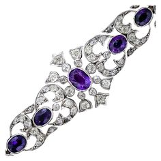 A rare, regal and astonishingly beautiful late-Victorian/early-Edwardian bracelet, circa 1890- 1900, in glorious purple and sparkling white (diamonds). This magnificent antique treasure is handcrafted in silver and 14 karat gold and is comprised of gracefully graduated diamond-set sections - plus the centerpiece - each of which is composed of a single faceted oval amethyst and an array of sparkling old mine-cut diamonds. Circa 1890-1900