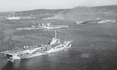 The forward elements of the new core of the British Eastern Fleet, pictured at Trincomalee in February 1944. In the foreground is HMS Unicorn, with the battlecruiser HMS Renown above and HMS Illustrious to the right. The cruiser partially obscured by smoke is either HMS Ceylon or HMNZS Gambia. The fresh arrivals from the Home and Mediterranean fleets have not yet been repainted in Eastern Fleet camouflage.