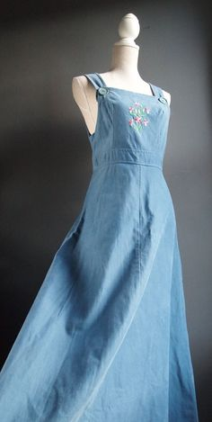 Fantastic powder-blue pinafore/jumper dress, with sweet floral embroidery on the bodice.  Flared maxi skirt.  Zip at the back with hook fastening.  Two straps can also be buttoned into place.  Perfect for summer!  Wear with fabulous wedges and a cotton tee for cool 70s vibes.  Spare button sewn onto tag.  No label but feels like heavy duty cotton/denim.  Vintage item with signs of wear and tear consistent with age and use: A couple of loose threads and snags.   Size: Small, please r...