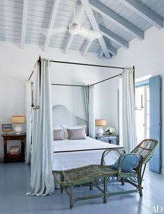 In a vacation home on the Greek island of Spetses, designer Isabel López-Quesada designed the master bedroom's curtained four-poster; an antique French chaise longue stands at its foot.