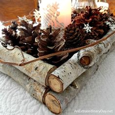 Candles, tree branches, pinecones and book paper snowflakes make a pretty centerpiece