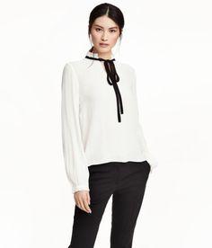 Kolla in det här! En v-ringad blus i skir, vävd kvalitet. Blusen har låg ståkrage med volangkant upptill och kontrastfärgat knytband. Lång ärm med knäppning och kort volang vid ärmslut.  - Besök hm.com för ännu fler favoriter.