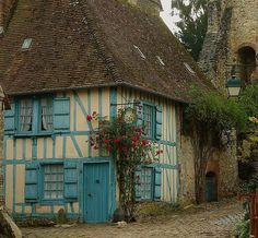 Tudor English cottage, cream with sky blue shutters. It's amazing what the right color can do to add charm!