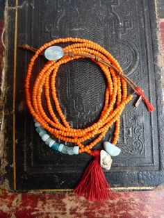 "theiainteriordesign: "" Bracelet 6 wraps of orange beads, with a red TASSEL, a shell and an amazonite… """