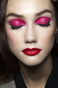 Heavy fuschia eyeshadow with eye liner and red lips.