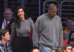Cracking a smile: Kim flashed her pearly whites as she followed Kanye back to their prime seats