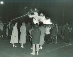 A crowd gathers around the University of Minnesota 1956 Homecoming Bonfire. #UMN #ForeverGolf