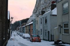 "The Hidden Houses of East Cliff below Dover Castle under Snow, Kent, England, UK. Early morning view (January 2013). When this area of land beneath the White Cliffs of Dover was first built upon it was considered ""extra-parochial"" (ie not subject to municipal rates). 57 and 58 are the ""First and Last"" pub (ex-Albion). Unseen on the left are the rear entrances to much grander properties that front onto ""East Cliff (Marine Parade)"". Urban Dover, Winter. See: http://www.panoramio.com/photo/8504..."