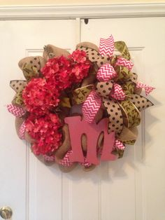 Burlap wreath with hydrangeas, multi-patterned ribbon, and glittered monogram decorations.