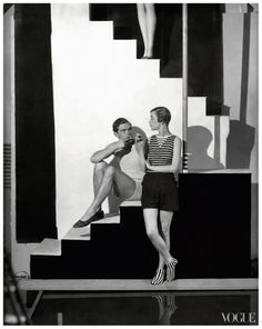 Bathing suits in Vogue – 1928-07-01 – Photo GeorgeHoyningen-Huene.  Original caption:Model, standing with back to a wall, smoking a cigarette, wearing a two-piece bathing suit with a black and white striped sweater over black flannel shorts with side buttons and striped bathing socks, by Schiaparelli, with man sitting on staircase, smoking