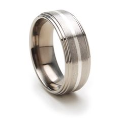 8 mm Titanium band with a raised center features a beautiful 1 mm Sterling Silver Inlay with a Stone finish and Polished finish on the sides.  This ring is sold on Renaissance Jewelry Company.