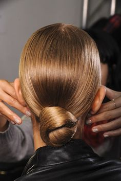 2013 Spring's Go-To Up-Dos: Ralph Lauren - The neat, sleek buns seen at Ralph Lauren would make the perfect summer party hairstyle. Fasten low at the nape of the neck and flatten any loose strands with hairspray or serum for a sleek finish.