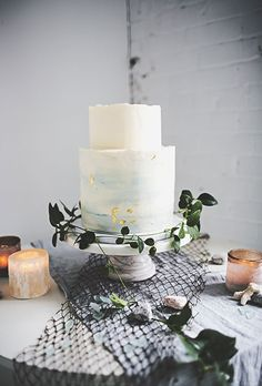 A two-tier chocolate truffle wedding cake with a blue-and-white honey sea salt buttercream and accented with gold leaf details | Brides.com