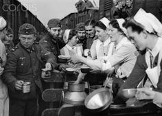 German Red Cross (DRK) nurses take care of the troops. On the back of the image is dated February 1941: A DRK helper gives out warm food to soldiers who travel through the train station Hasselt. Photo: Berliner Verlag/Archiv