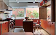"""A antiga cozinha ganhou status de espaço gourmet. Os armários foram revestidos de laminado laranja. O arquiteto André Vainer adora usar cor em seus projetos. """"O branco é muito tirânico: reflete a luminosidade e ofusca a visão"""", opina"""