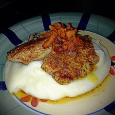 Blackened Tilapia topped with buttered carrots over a bed of creamy mashed potatoes