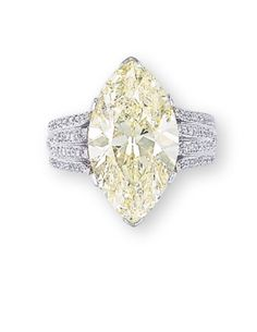 A COLOURED DIAMOND AND DIAMOND RING. Set with a fancy light yellow marquise-cut diamond weighing 8.05 carats, to the pavé-set brilliant-cut diamond gallery and half-hoop, mounted in platinum, ring size 5.