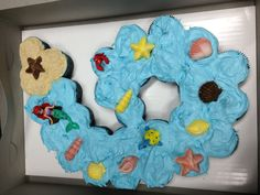 """Maggie's 6 year old cupcake cake. She wanted chocolate cupcakes with vanilla icing. I tinted the icing blue, made a """"beach"""" out of vanilla wafer crumbs, added candy seashells and a """"Little Mermaid"""" Playset."""
