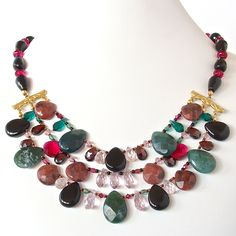 Amadeus: Gemstone Statement Necklace. This gorgeous statement piece is brimming with striking semi-precious drops of black onyx, moss agate, rose quartz and rhodonite. This handcrafted knockout will add glamour and elegance to your look. https://earthandmoondesign.com/collections/necklaces/products/amadeus-gemstone-statement-necklace