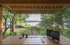 This enchanting cabin features an expansive, 10-foot-wide insulated panel of glass which frames a panoramic view of the water from the workstation. The desk and cabinets are by Korben Mathis Woodworking; the desk lamp is from TaoTronics. #dwell #moderndesign #modernarchitecture Tiny Studio, 3d Studio, Prefabricated Houses, Prefab Homes, Pump House, Cabin In The Woods, Little Cabin, Backyard Retreat, Cozy Cabin