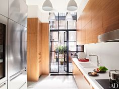 West Elm pendant lights illuminate the kitchen, which is equipped with Varenna by Poliform oak cabinetry, a Sub-Zero refrigerator, a Corian backsplash and countertop, and Dornbracht sink fittings.