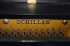 Piano vertical americano marca Schiller color negro.