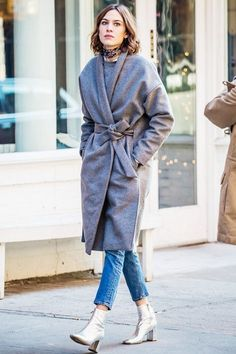 Menswear-inspired grey wrap coat, tapered mom medium-wash mom jeans, silk scarf wrapped around neck, and metallic pointy-toe, block-heeled booties.