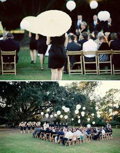 Bridesmaid parasols instead of bouquets.